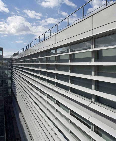 Los parasoles horizontales que envuelven el edificio lo convierten en una construcción imponente y moderna donde se conjugan los efectos de luces y sombras.
