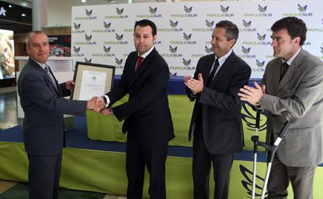 Juan Novillo, gerente de Consumo y accesibilidad entrega el certificado al director del centro comercial Parquesur, Sergio García