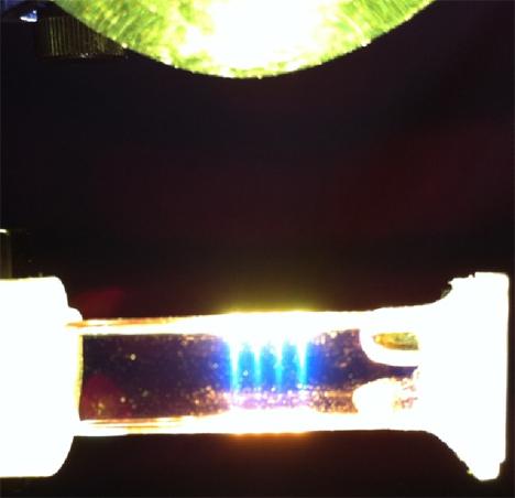 """En la imagen se observa el proceso de Up-Conversion (UC) en un sistema, a escala laboratorio, que puede acoplarse a celdas fotovoltaicas. En este caso, el sistema transforma luz """"verde"""" de baja energía en """"azul"""" de mayor energía."""