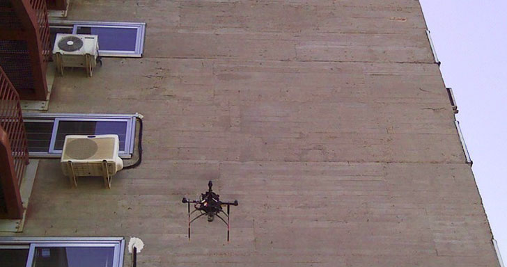 Un dron volando junto a un edificio para detectar posibles patologías del mismo.