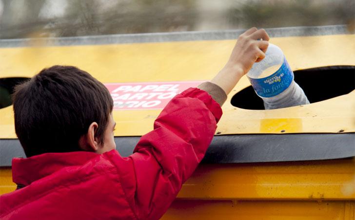 Niño reciclando en el contenedor amarillo. El reciclaje de plásticos se multiplica por 7 en España, segú un infomre de Cicloplast.
