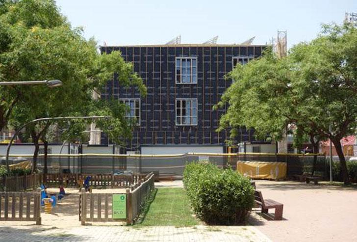 Vista de la fachada este con paneles fotovoltaicos en la coronación del edificio.