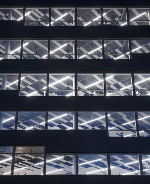 Grandes ventanales cubren la fachada del edificio permitiendo la entrada de luz natural y las vistas al fiordo.